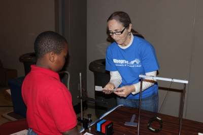 A representative from Bluegrass Community and Technical College works with one of the elementary students at the Energy Fair Dec. 9 in the UK Student Center Grand Ballroom.