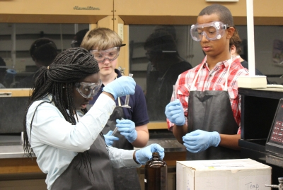 Stephanie Bamfo (left) conducts a chemistry experiment with her fellow STEAM Academy students at UK.