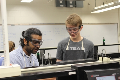 Bharath Kumar (left), a doctoral student in STEM education at UK, helps a STEAM Academy student with a chemistry project.